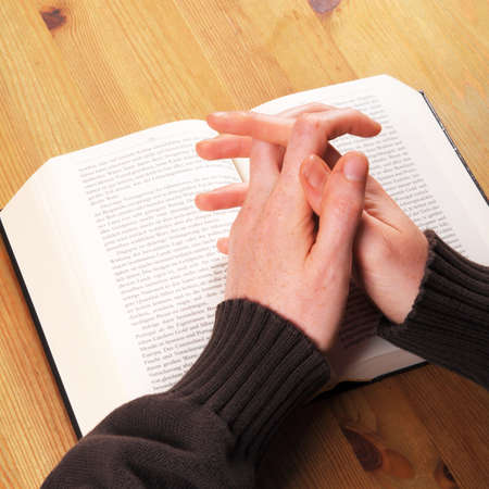 confession: praying hands and book showing christian religion concept Stock Photo