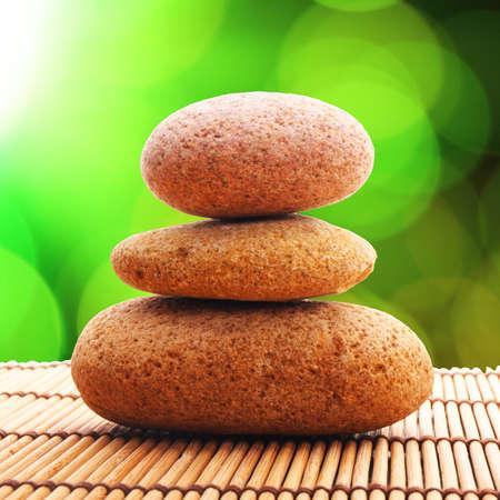 Zen-Steine mit grünen Blättern und Exemplar, die zeigen, wellness