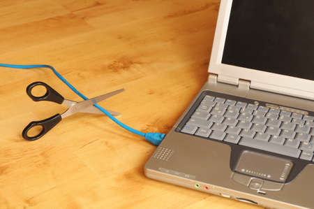 wlan: wireless network or wlan concept with laptopn scissors and cable Stock Photo