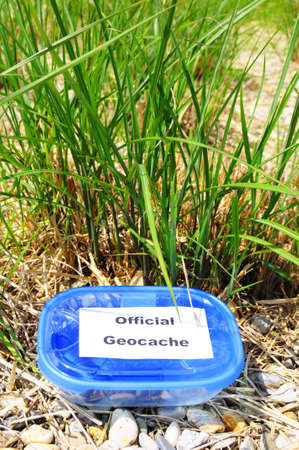 caching: geocaching concept with blue geocache box showing outdoor sports concept Stock Photo