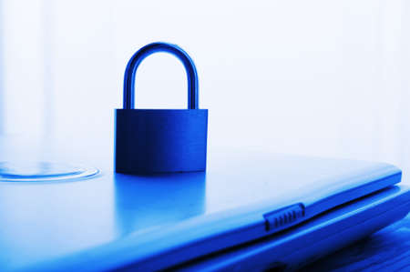 privat: notebook and padlock showing internet or data security concept in blue Stock Photo