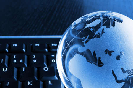 international internet: globalisation concept with glass planet on computer keyboard and copyspace