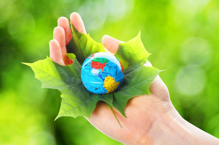 environmental safety: globe and leaf in hands for environmental conservation Stock Photo