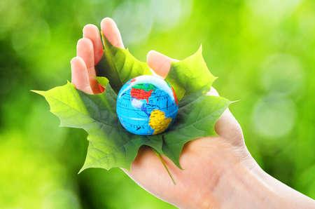 Globus und Leaf in Händen für Umweltschutz