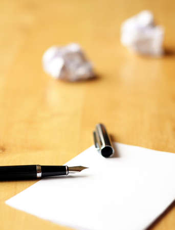 pen and paper in a wooden desktop showing creativity concept
