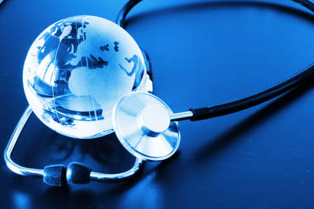 ecology eco environment or global warming concept with glass globe and stethoscope photo