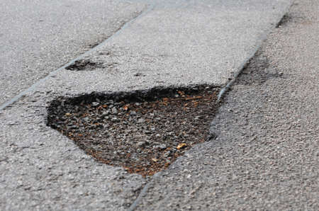 pothole road damage or pot hole concept with street photo