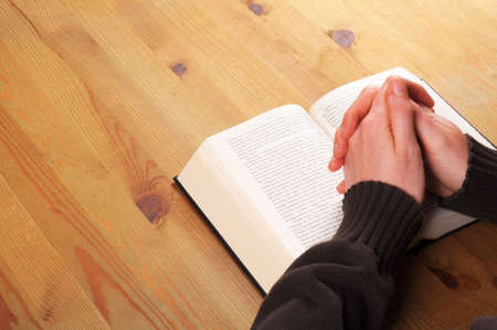 praying hands and book showing christian religion concept Stock Photo