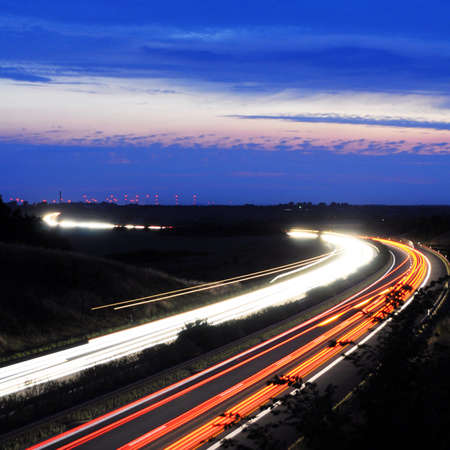 light trail: night traffic motion blur on highway showing car or transportation concept