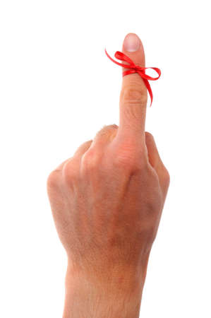 reminder concept with hand and red bow isolated on white background photo