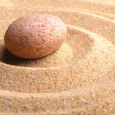 zen garden with stone or pebble on sand with leaf photo