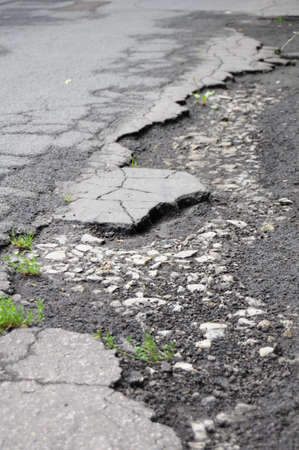pot hole: pothole road damage or pot hole concept with street
