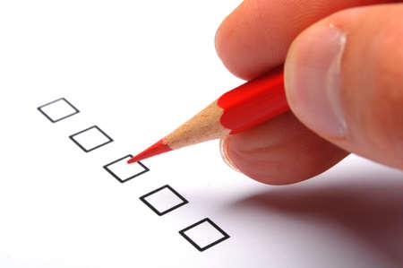 questionaire: formulario de la encuesta de calidad con l�piz rojo mostrando el concepto de marketing Foto de archivo