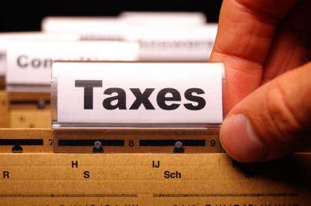 taxes: impuestos o concepto de impuestos con la palabra en el �ndice de carpeta de negocio Foto de archivo