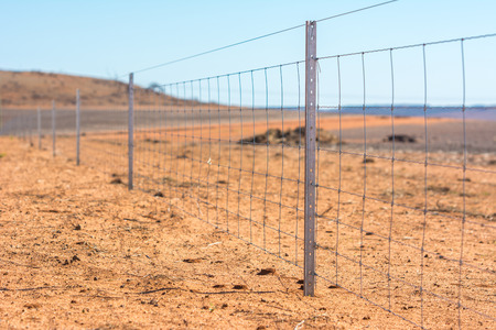 bearded wires: Barbed wire fence on dry land at west Australia Stock Photo