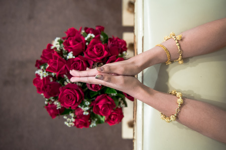 Thai wedding hand of a bride prepare for receiving holy water from elders and  flower  brunch in wedding ceremony. Stock Photo