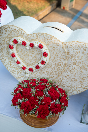 heart shape box with red rose for gift at wedding reception in Thai wedding party. Wedding attributes.  luxury wedding gift box with roses greeting for bride and groom. close up