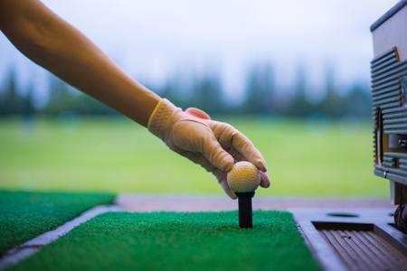 Woman golfer's hand holding ball on tee with golf course background. close up of golf players hand placing ball on tee at driving range in sport club.
