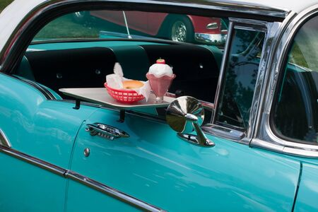 tray with burger and milk shake on classic car at drive in