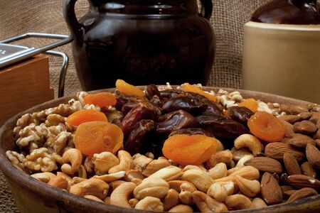 stoneware: Tray with walnuts, almonds, cashews, dates and apricots in a rustik setting with stoneware Stock Photo