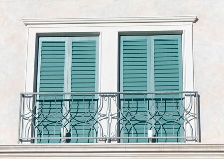 two windows with closed green shutters photo