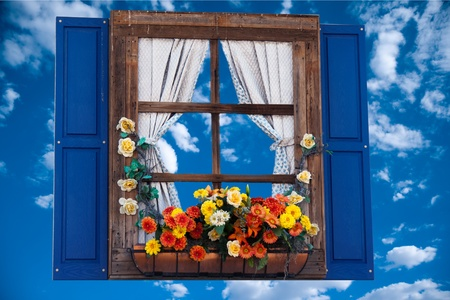 Land stijl venster met bloemen, plantenbak, rolluiken en gordijnen, hemel Stockfoto