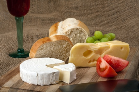 Norwegian Jarlsberg and Camembert with Italian white bread on wooden cutting board photo