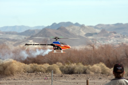 power operated: RC helicopter in flight in front of mountains