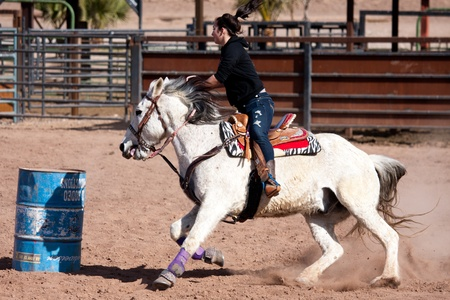 Women horse barrel race in corral in las vegas