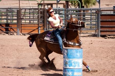 Women horse barrel race in corral in las vegas