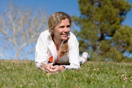 mature woman laying in grass in a park smiling photo