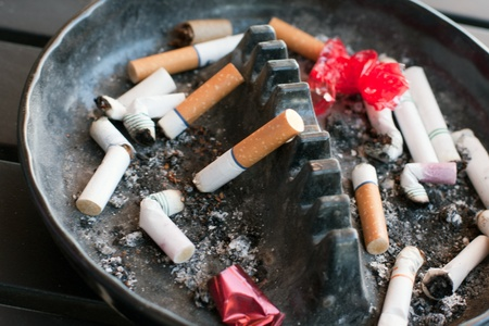 ashtray full with buts and lipstick and paper Stock Photo