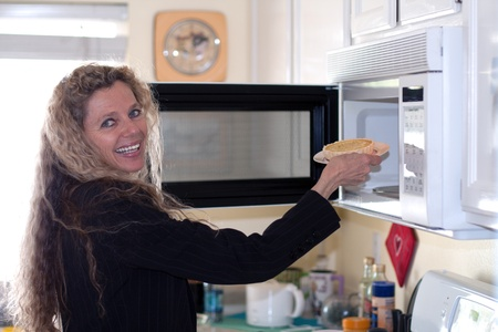 Mature woman loads food into the microwave oven photo