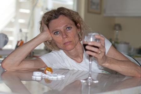 drogadicto: mujer madura addictet consumo de vino y pastillas Foto de archivo