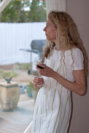 Lonely mature womanlooking out a window drinking wine photo