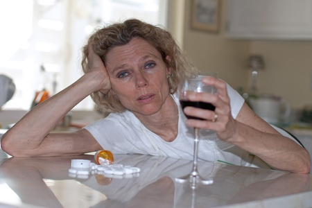 mature addictet woman drinking wine and pills
