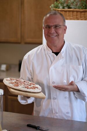 chef with frozen pizza in kitchen presenting Stock Photo - 13222571