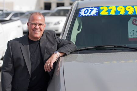 car salesman on lot with price sticker on cae selling photo