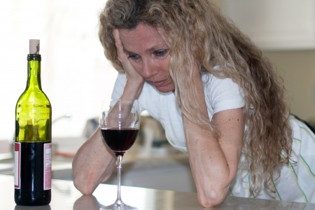Depressed woman, drinking wine in kitchen during the day Stock Photo