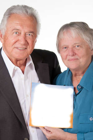 Senior couple holding up a book Imagens