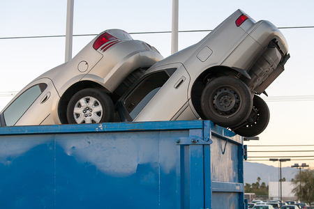 crushed aluminum cans: 2 junk cars in a dumpster