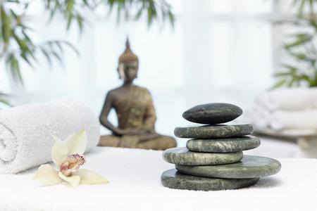 Bhudda and hot stone on massage bed Standard-Bild