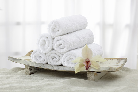 Rolled towels in wood Bowl with Orchid against a white background Standard-Bild