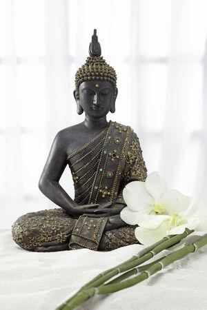 mit: Buddha Statue mit Orchideenblüte und Bambusstäben Stock Photo