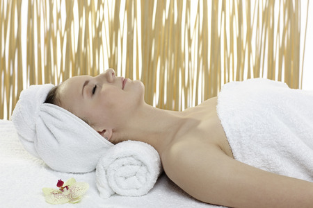 Young beautiful woman getting spa treatment on a white background photo