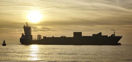 Cargo ship at sunset Standard-Bild