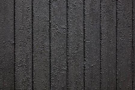 Board wall made of black tarred wood