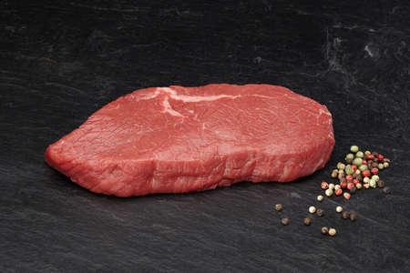 Beef steak on black slate plate with colorful pepper Standard-Bild