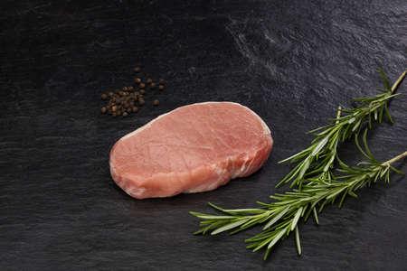 Veal steak prepared for frying on black slate plate