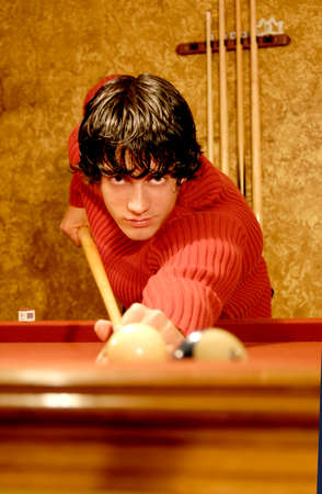 An attractive and handsome young man plays the game of pool or billiards, holding his cue stick. Фото со стока
